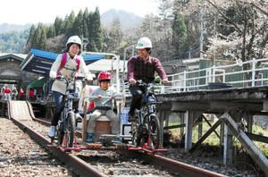 運行開始の初日にレールマウンテンバイクを満喫する親子連れら=飛騨市神岡町で