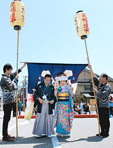 花嫁のれんをくぐり、愛を誓う新郎新婦=七尾市生駒町で