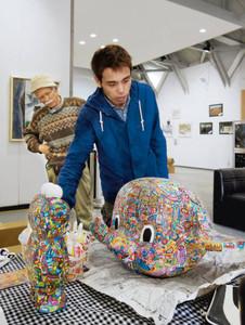 展示に向け作品を持ち込んだウメツさん(右)。左は館主の中田さん=羽咋市滝町で