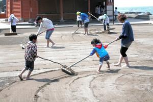 塩田で塩づくりを体験する親子連れら=珠洲市清水町で