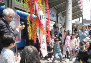 くす玉を割り、運行延長と乗客10万人突破を祝う人たち=高岡駅前電停で