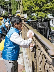 10日の「渡り初め式」を前に欄干を拭く参加者=名古屋市の納屋橋で