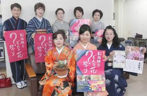 「松阪撫子どんな花?祭り」のポスターを手に来場を呼び掛ける「ミズ・ネットワーク松阪」のメンバーら=松阪市役所で