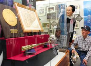 展示が始まった金色のバットと表彰状、盾を眺める来館者=能美市山口町で
