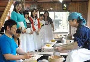 参加者が見守る中、若尾圭介さん(左)の指導を受け作陶する亀吉(右)=多治見市住吉町の虎渓窯で