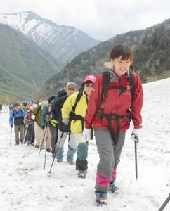 長い列になって登る参加者=大町市の針ノ木雪渓で