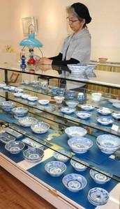 伊万里焼の器やガラス製ランプを並べる小島さん=彦根市のギャラリーコジマで