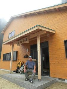 新築され、5年ぶりに営業を再開した日向小屋と梅田さん=菰野町の御在所岳で