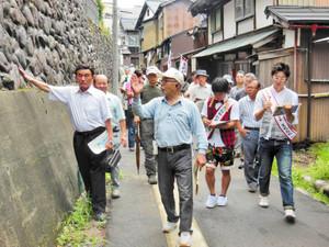 丸屋仁志さん(前列中)の案内で「七里壁」を見学するクレヨンのいとうさん(前列右)ら=勝山市本町2で