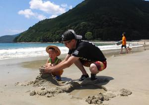 海開きした三木里ビーチで砂遊びを楽しむ親子=尾鷲市三木里町で