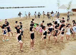 広くなった砂浜で初泳ぎのため体操をする子どもら。奥に見えるのが離岸堤=高岡市太田の松太枝浜海水浴場で