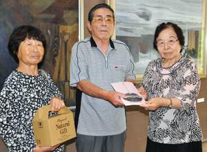 中島さん(右)から記念品を受け取る牧野さん夫妻=阿智村の満蒙開拓平和記念館で