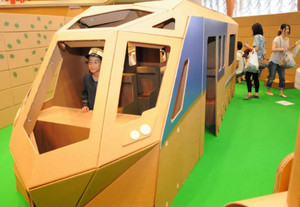 段ボールで作られた特急電車「しまかぜ」の中に入って楽しむ子どもら=四日市市諏訪栄町の近鉄百貨店四日市店で