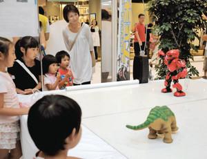 踊りを披露する赤いロボットに見入る親子連れら=四日市市富州原町のイオンモール四日市北で