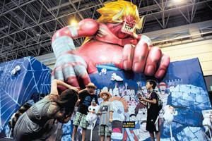 天井に届くほど大きなキャラクターの前で記念写真を撮る来場者ら=静岡市駿河区で