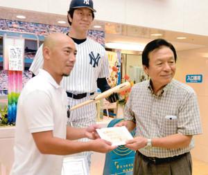 佐倉市の職員(左)から松井さんに向けて書かれたメッセージカードを受け取る父昌雄さん=能美市山口町で
