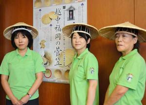 左袖にイメージキャラ「かさぼんこ」があしらわれているポロシャツを着る保存会スタッフら=高岡市福岡庁舎で