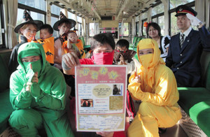 PRチラシを手に参加を呼び掛ける仮装姿の関係者ら=関市元重町の長良川鉄道関駅で