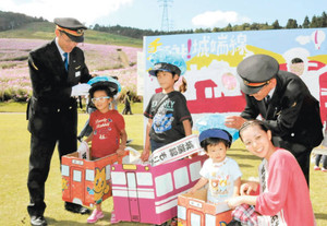 「城端線に乗ろう」啓発ブース前で、段ボールの城端線列車に入り記念写真を撮る子どもたち=砺波市五谷で