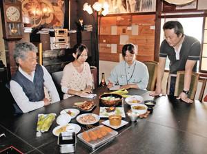 グラタンやにぎりずしなど、氷見産マコモタケの料理の説明をする飲食店主(右)ら=氷見市朝日本町で