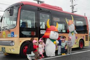 ひこにゃんバスの運行開始を祝い園児たちとポーズを取るひこにゃん=彦根市大東町で