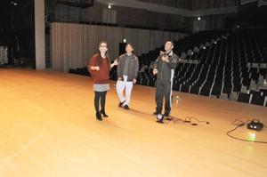 ホールの舞台で照明の具合などを確認する真寿美さん(左)らスタッフ=下呂市の下呂交流会館で