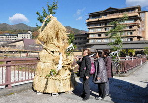 大きな「本湯屋守様」を見上げる温泉客=阿智村の昼神温泉郷で