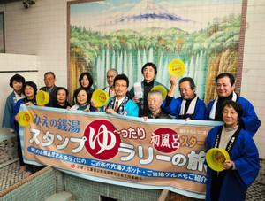 浴場に描かれた富士山のタイル絵の前で、スタンプラリーをPRする銭湯経営者たち=松阪市春日町の春日温泉で