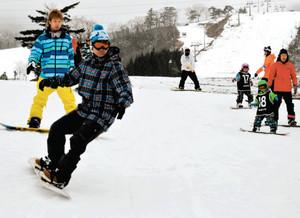小雪が舞う造雪ゲレンデを滑るスノーボーダーら=郡上市高鷲町のダイナランドで