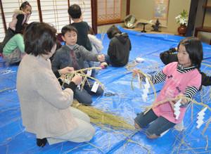手作りしたしめ縄を見せ合う子どもたち=高岡市横田町で