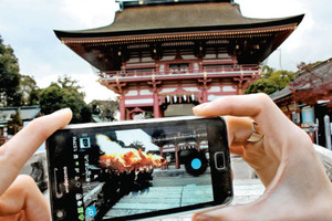 津島神社の楼門前で、スマートフォンの画面に出てきた開扉祭の画像=津島市神明町で