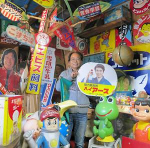 ホーロー看板を手にして「昭和の空気を楽しんで」と話す佐溝力さん(中央)=豊川市大橋町の看板と広告の資料館で