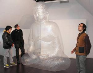 「浮遊体」を解説する早瀬さん(右)=池田町草深の極小美術館で