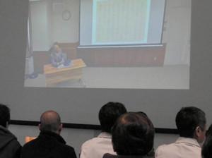 大型スクリーンによるイ病の語り部の上映を見る来場者=富山市大手町で