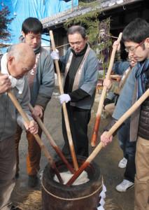 千本杵を使って餅をつく参加者=伊賀市島ケ原で