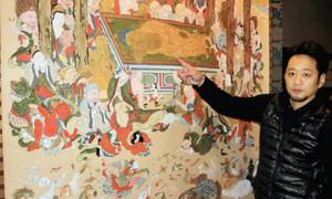 涅槃図の前で修復作業を振り返る辻村さん=鳥羽市船津町の白言寺で