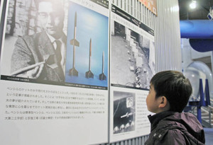 日本の宇宙開発の父・糸川英夫博士のパネルを見上げる子ども=坂井市のエンゼルランドふくいで