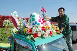 パレードを先導する軽トラックの屋根に造花を飾り付ける佐藤さん=安城市赤松町のデンパークで