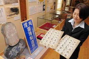 蚕の卵を張り付けた「種紙」(写真右手前)や犬塚蚕種製造所の看板が展示された会場=豊田市近代の産業とくらし発見館で