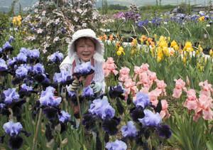 亡き夫と一緒に続けてきたアイリス園で笑顔を見せる田戸ヒデ子さん=豊丘村で