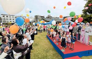 イベントの成功を祈って風船を飛ばす参加者たち=あわら市のあわら温泉湯のまち広場で