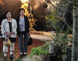 ホタルを模したLEDの明かりを眺める来場者=米原市のヒロヤマガタ湧水ギャラリーで