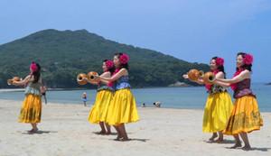 フラダンスを披露して海開きを祝うカイラニのメンバーたち=志摩市志摩町御座の御座白浜海水浴場で