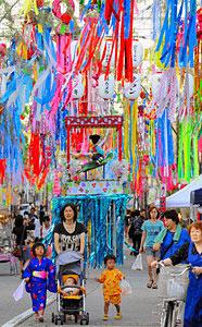 七夕で飾られた歩行者天国の通りを歩く親子ら=入善町入膳で