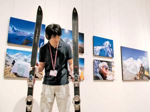 三浦雄一郎さんのエベレスト登頂を記録した写真やゆかりのスキー板が並ぶ会場=南砺市福光美術館で